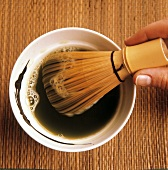Beating Matcha powder and water with bamboo whisk
