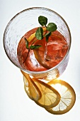 Fruit iced tea with lemon slices and ice cubes