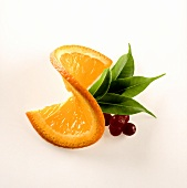 Slice of orange with cranberries and leaves