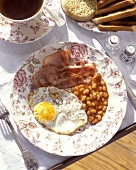 English breakfast with fried egg, bacon and baked beans