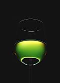 Filled white wine glass against green light