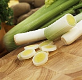 Leek and leek slices on wooden platter, vegetables behind