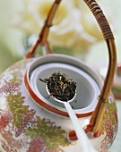 Black tea on spoon above Asian teapot