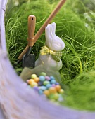 Decorative Easter bunny & sugar eggs on Easter grass in basket