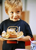 Small boy holding plate with apple cake