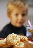 Plate of sweet yeast pastries, with small boy behind