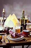 Rustikal gedeckter Tisch mit Brezel, Bier, Wein und Kerzen