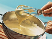 Whisk with sponge mixture above a bowl of sponge mixture