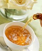 Tee wird in eine Teetasse eingeschenkt