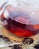 Black tea leaves and black tea in glass teapot