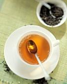 Tasse Tee mit Teelöffel, dahinter Teeblätter