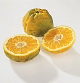 Whole and halved ugli fruit