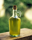 Olive oil in bottle with handles & cork on a wooden board