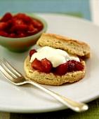 Scone spread with strawberries and vanilla cream