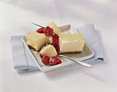 Two pieces of cheesecake with raspberry sauce