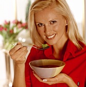 Woman holding a bowl of vegetable soup
