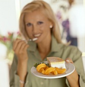 Woman holding plate with piece of gateau & apricot wedges