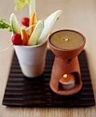 Vegetables sticks in beaker, warm anchovy dip beside it