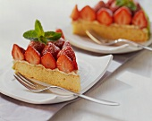Two pieces of strawberry gateau with lime cream on plates
