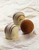 Two chocolates with white chocolate glaze & a truffle
