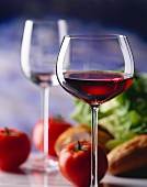 A glass of young red wine, tomatoes, salad & bread behind