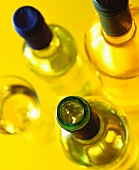 Three white wine bottles and a wine glass (from above)
