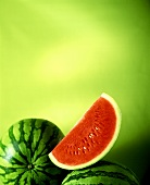 Slice of watermelon and two whole melons