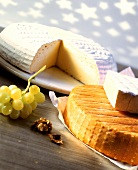 Two types of cheese, white grapes and walnut