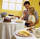Father and daughter eating at cake buffet