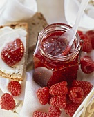 Raspberry jam in jar and on bread