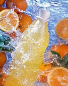Bottle of orangeade and oranges in splashing water
