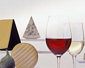 Verschiedene Käsesorten, zwei Gläser Wein und eine Feige