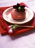 Strawberry ice cream with chocolate flower on sponge base