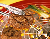 Grilled frikadeller with grill tongs and meat thermometer
