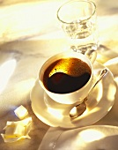 Cup of black coffee, glass of water & sugar cubes
