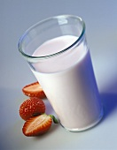 A glass of strawberry milk and fresh strawberries