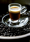 "Espresso (""lengthened"") in glass cup on coffee beans"