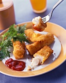 Fish fingers with ketchup and salad garnish