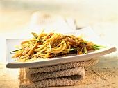 Spaghetti salad with vegetables, ham and sesame