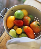 Tomatoes of various colours and sizes in metal strainer