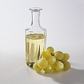 Grape seed oil in a glass bottle, grapes beside it