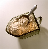 Wholemeal flour in glass container with small scoop