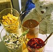 Muesli ingredients in glasses, teddy bear behind