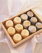 Several Crotin de Chavignol cheeses in a wooden box