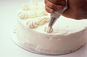 Decorating a sponge cake with cream