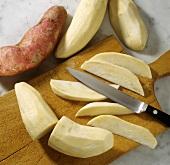 Cutting peeled sweet potatoes into wedges lengthwise