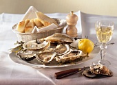 A plate of oysters, with lemon, baguette and wine