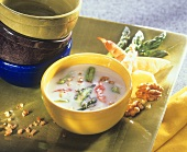Creamed cheese soup with green asparagus and shrimps