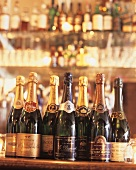 Various champagne bottles on a bar counter