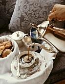 Frühstückstablett: Kaffee wird aus Silberkanne eingeschenkt
